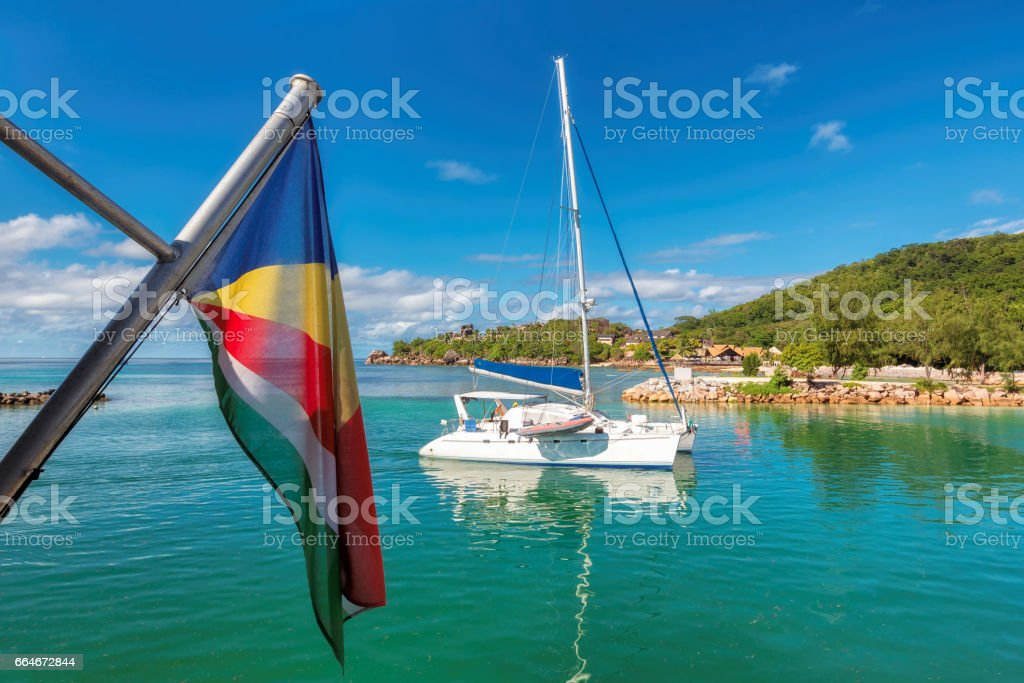 Tropical island with sailing yacht and flag of Seychelles. stock photo