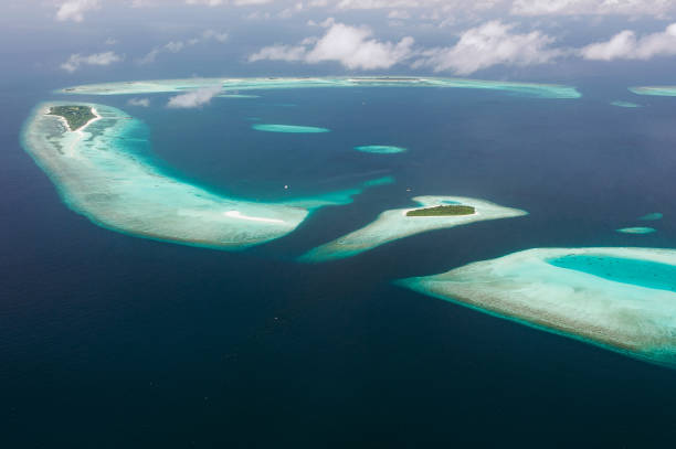 Tropical islands and atolls in Maldives in Indian Ocean from aerial view. Piece of paradise on the Earth. Good choice for vacation. Beautiful top view for wallpaper. - foto stock