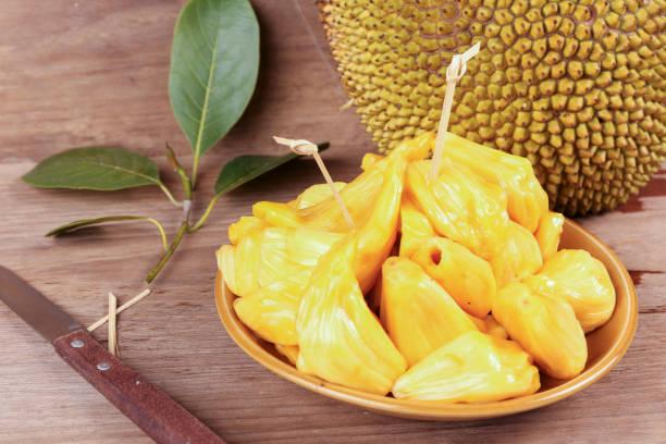 tropical jack fruit auf dem holzhintergrund - jackfrucht stock-fotos und bilder
