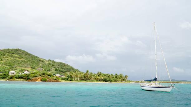 tropischer ozean und strand mit segelboot yacht in den tobago cays, st. vincent und den grenadinen, karibik. - kingstown stock-fotos und bilder