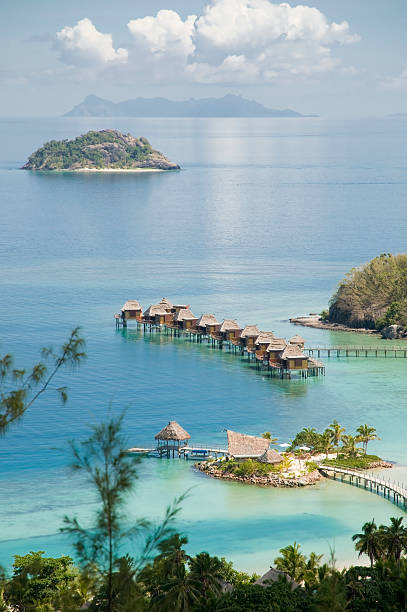 tropical ocean resort with huts in the water - fiji stock photos and pictures