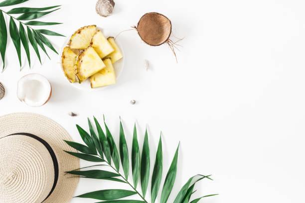 Feuilles de palmiers tropicaux, chapeau, ananas, noix de coco. Concept de l'été - Photo