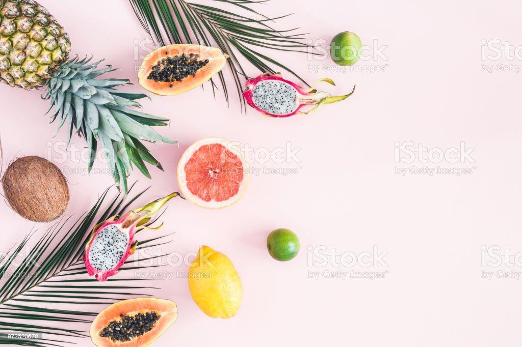 Tropical palm leaves, pineapple, coconut, papaya, dragon fruit, orange stock photo