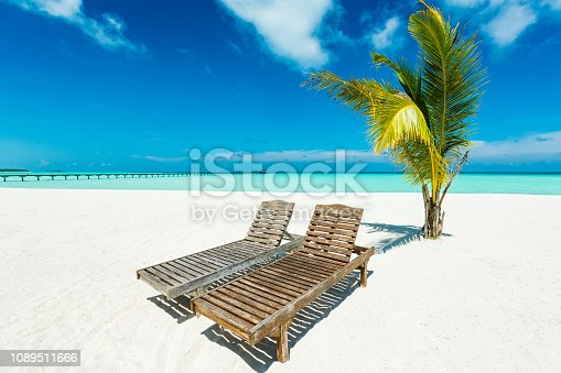 Lounge chairs at tropical paradise beach at Dhiffushi Holiday island at South Ari atoll, Maldives. Beautiful turquoise Indian ocean sea with white sand. Luxury travel holidays background. Property released.  Photo taken by Sony a7R II, 42 Mpix.