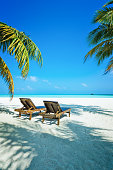 Tropical paradise beach at Dhiffushi Holiday island at South Ari atoll, Maldives. Beautiful turquoise Indian ocean sea with white sand. Luxury travel holidays background. Property released.
