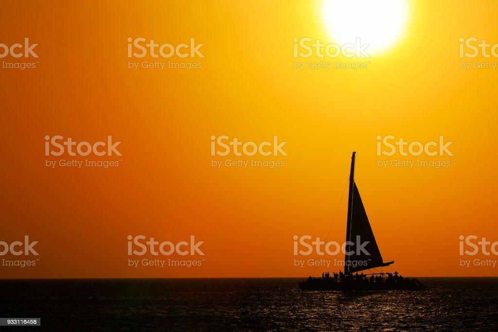 Tropical paradise: sailboat yacht sailing at dramatic sunset - Aruba, Caribbean sea stock photo