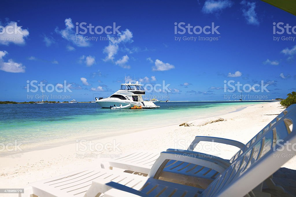 Tropical paradise with lounge chairs umbrella and a yacht stock photo