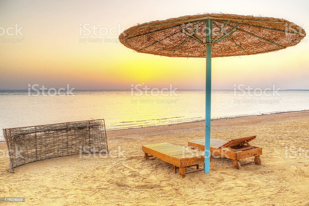 Tropical parasol on the beach of Red Sea at sunrise stock photo