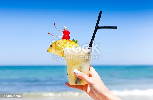Tropical pina colada drink with pineapple in a hand of the woman on a tropical beach with ocean in the background