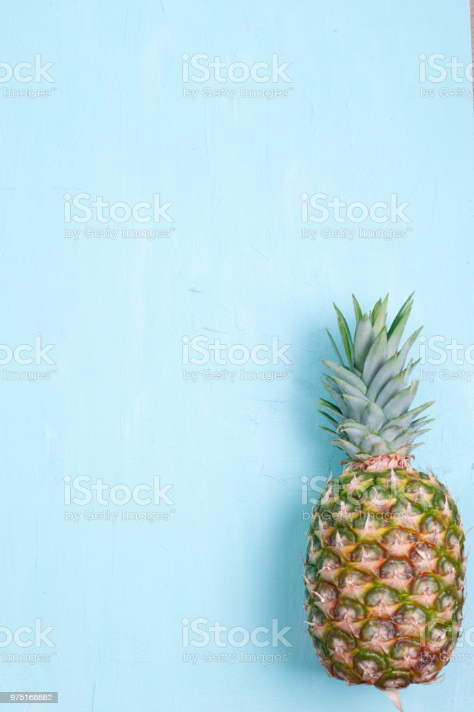 Tropical Pineapple fruit on a blue background. Free space for text....