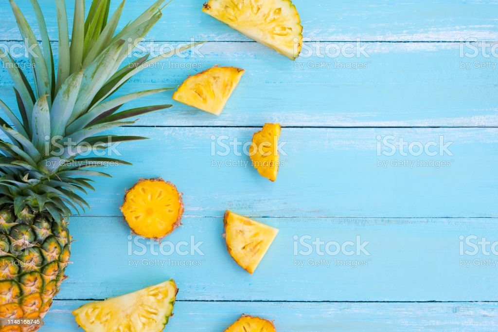 Tropical pineapple slices on wood plank blue colors. frame layout...