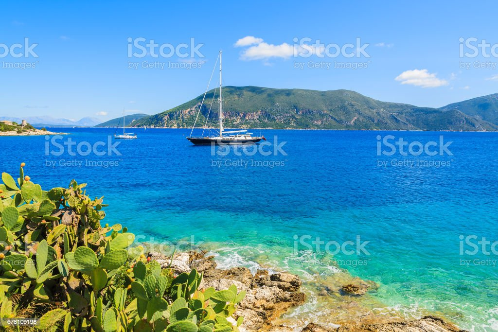 Tropical plants on coast of Kefalonia island with luxury yacht boat on sea in background, Greece stock photo