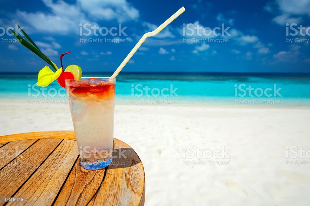 Tropical, refreshing cocktail on a white sand beach royalty-free stock photo