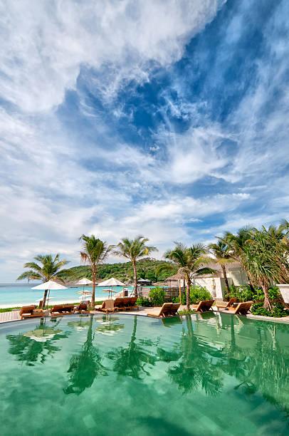 tropische resort-pool mit palmen und ozean - ferienhaus thailand stock-fotos und bilder