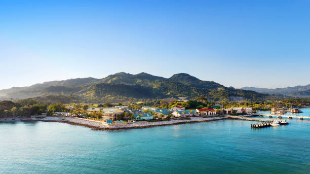Tropical resort with pier Panorama of tropical island with port and resort bay of water stock pictures, royalty-free photos & images