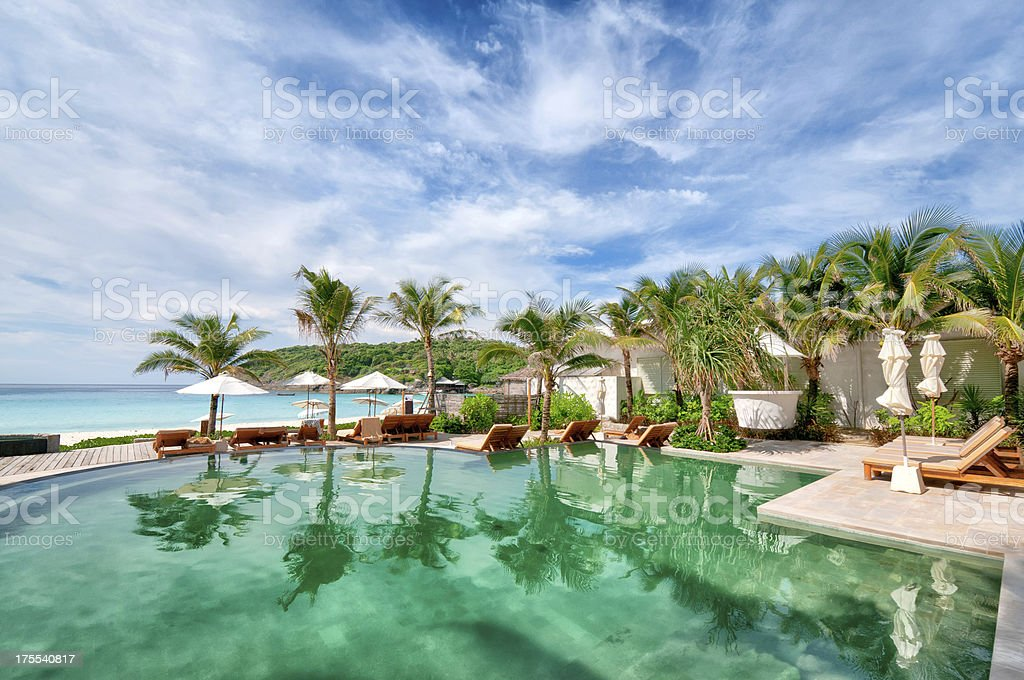 Tropical resort with pool and palm trees near the ocean stock photo