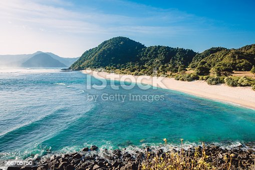 Tropical sandy beach and waves for surfing in ocean with blue sky