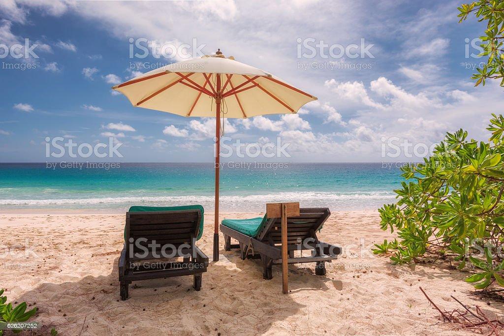 Tropical sandy beach with umbrella and beach chair - foto de stock