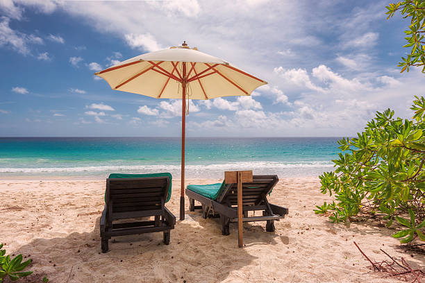Tropical sandy beach with umbrella and beach chair Tropical sandy beach with umbrella and beach chair goa stock pictures, royalty-free photos & images
