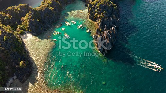 Tourist boats over tropical lagoon and coral reef, aerial view. Small lagoon with turquoise water. El nido, Philippines, Palawan. Summer and travel vacation concept.
