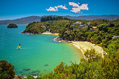 Beautiful tropical secluded Bay with Sandy Beach on a sunny day with people swimming and sailing