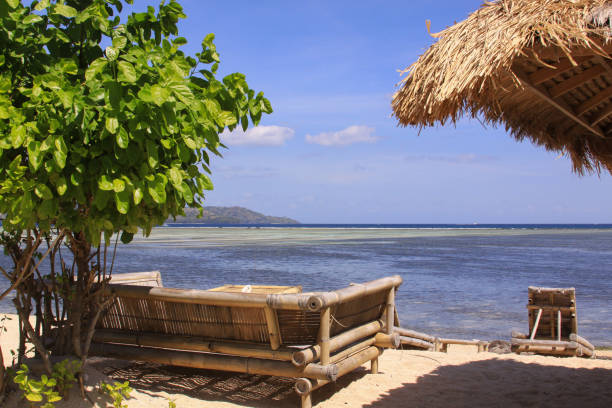 Tropical straw umbrella and sofas at beach bar stock photo