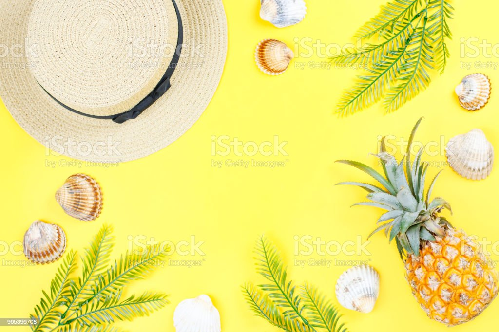 Tropical summer concept with woman fashion accessories, leaves and pineapple on yellow background. Flat lay, top view royalty-free stock photo