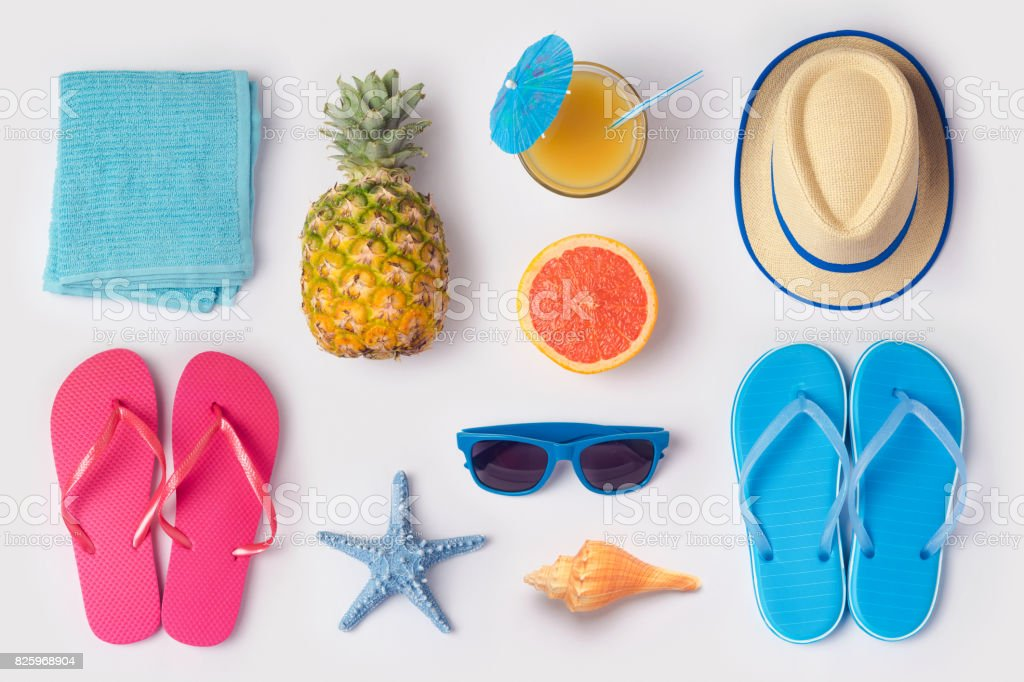 Tropical summer vacation concept with pineapple, juice and flip flops organized on white background. View from above. Flat lay foto stock royalty-free