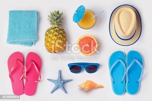 istock Tropical summer vacation concept with pineapple, juice and flip flops organized on white background. View from above. Flat lay 825968904