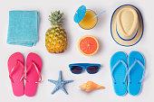 白い背景の上にパイナップル、ジュース、フリップフ ロップ熱帯の夏の休暇の概念が構成されています。上からの眺め。フラットを置く