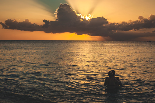 A young couple holding each other while bathing in the tropical sea watching the sun low on the horizon. It could be either sunrise or sunset. The ocean is calm.