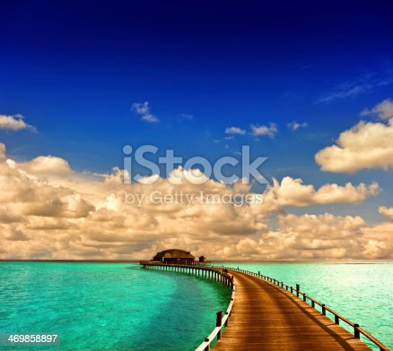tropical sunset seascape. overwater bungalow with jetty with dramatic blue sky