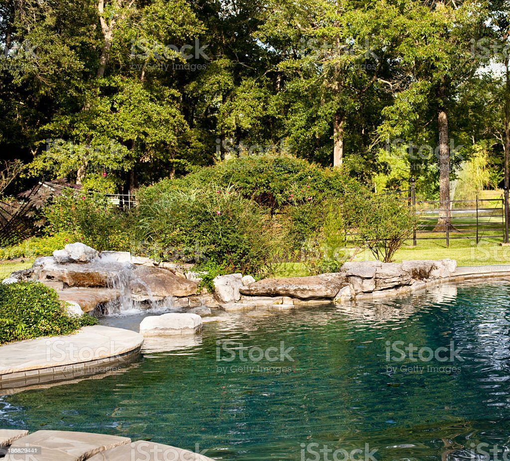 Tropical swimming pool with rock waterfall. stock photo