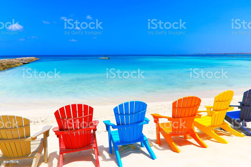 Tropical turquoise Beach with colorful outdoor adirondack chairs, Aruba, Caribbean sea stock photo