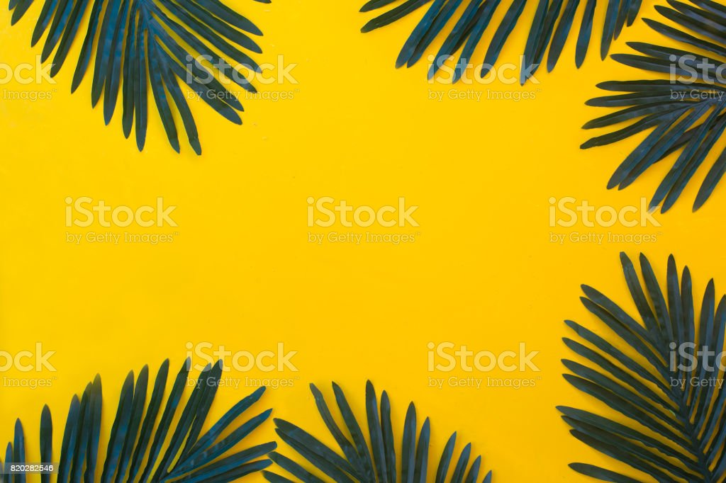 Tropical vacation and beach sand theme yellow colored background with dark green palm tree leaves stock photo