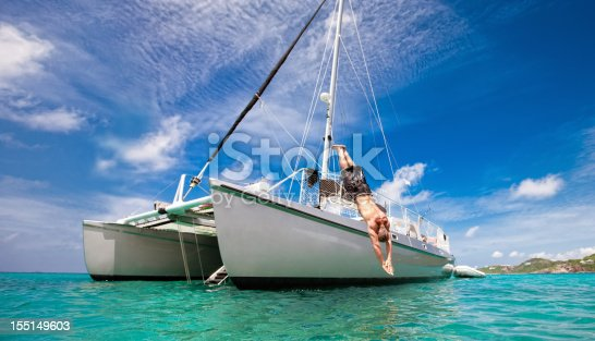 A mature man enjoys his vacation by diving off of the deck of a catamaran sail boat into the turquoise waters of the Caribbean on a beautiful day.