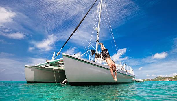 tropical vacation: man diving off sailboat - katamaran bildbanksfoton och bilder