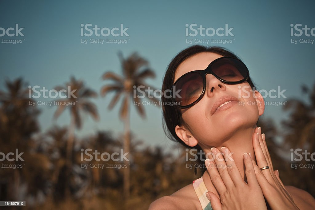Tropical vacation Woman wearing sunglasses relaxing at sunset against coconut palm trees.  30-34 Years Stock Photo