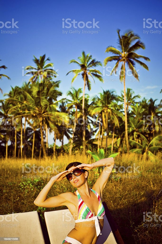 Tropical vacation Woman wearing bikini sunbathing on deck chairs with idyllic coconut palm grove in the background, Old Goa in India. Adult Stock Photo