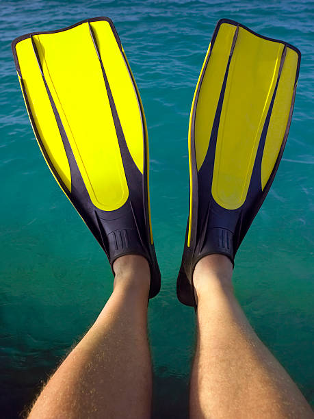 Tropical Vacation Man wearing flippers on a tropical vacation in the Maldives in the Indian Ocean diving flipper stock pictures, royalty-free photos & images