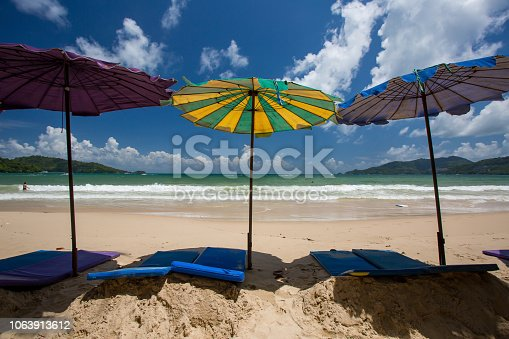 istock Tropical vacation scene with sun beds and sun umbrellas on the exotic coast 1063913612