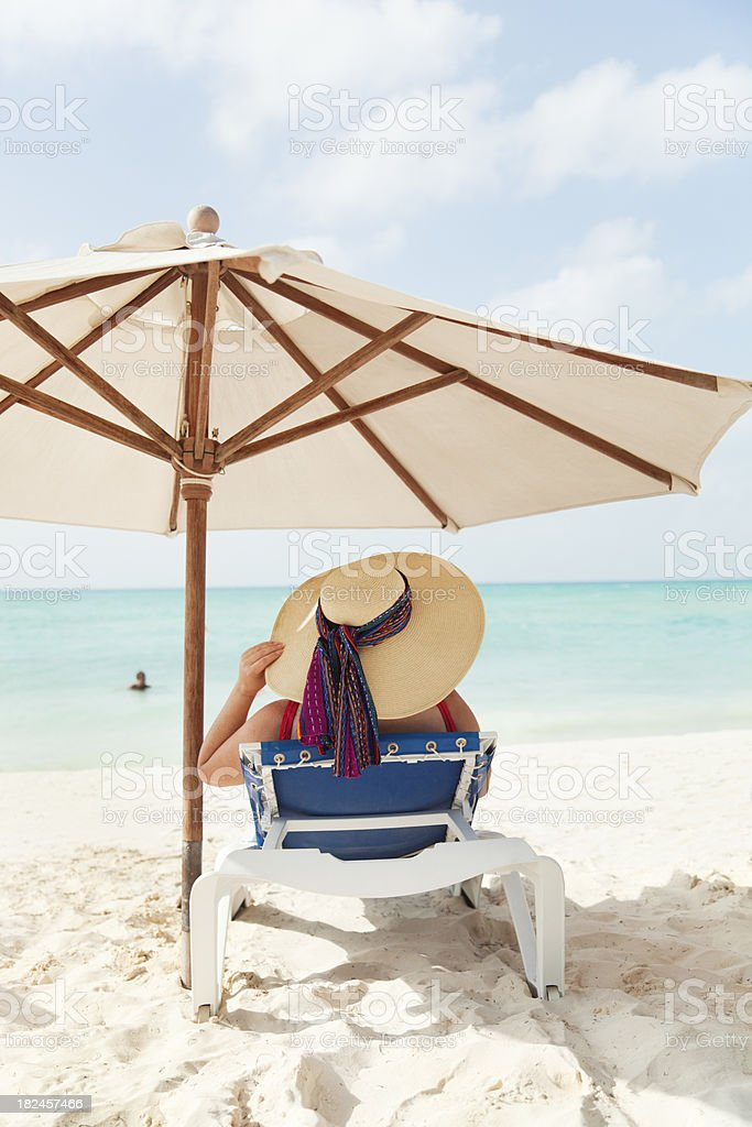 Tropical Vacation Woman Sunbathing Relaxing on the Beach Vt royalty-free stock photo