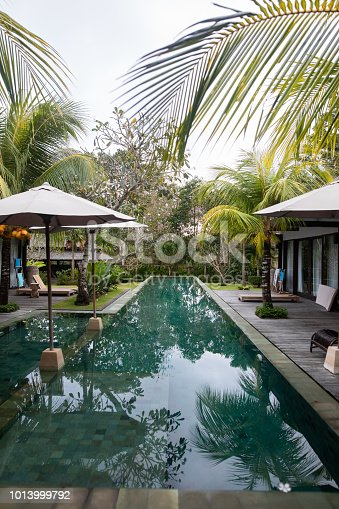 Tropical villa among palm trees at swimming pool with turquoise water