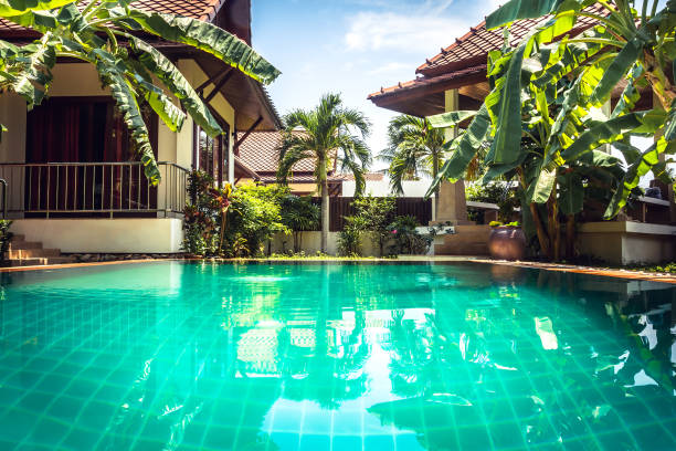 tropische villa unter palmen am pool mit türkisblauem wasser - ferienhaus thailand stock-fotos und bilder