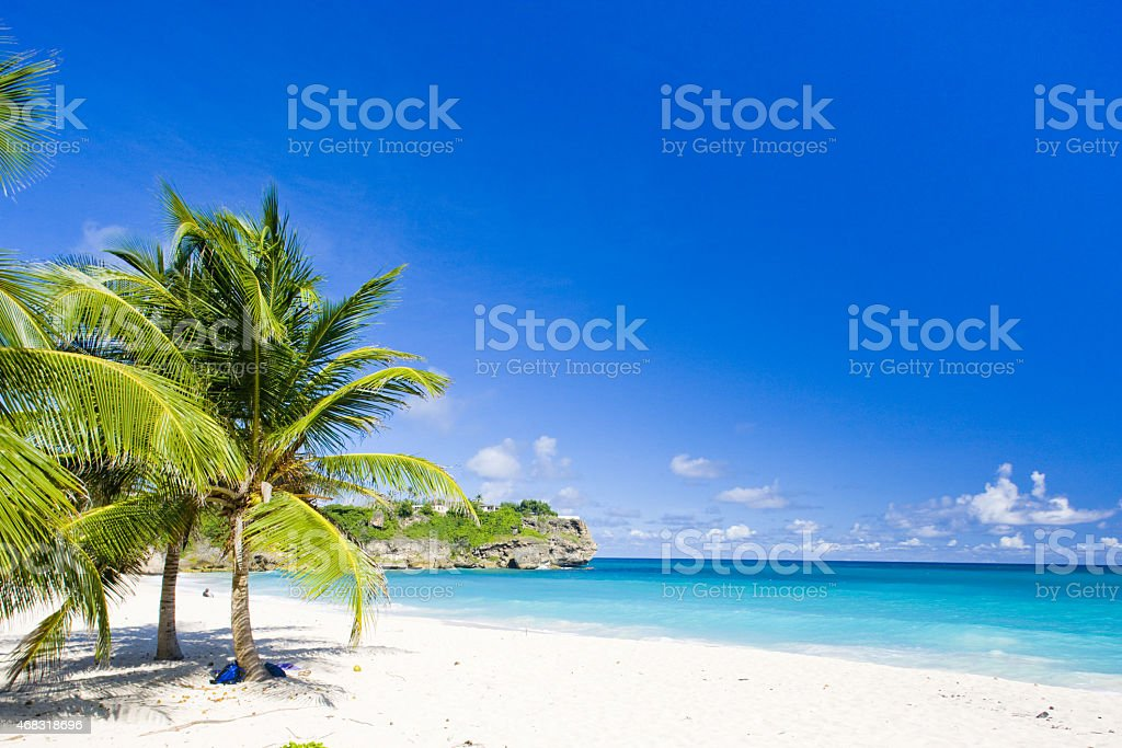 Tropical white sand beach paradise against a blue sky stock photo