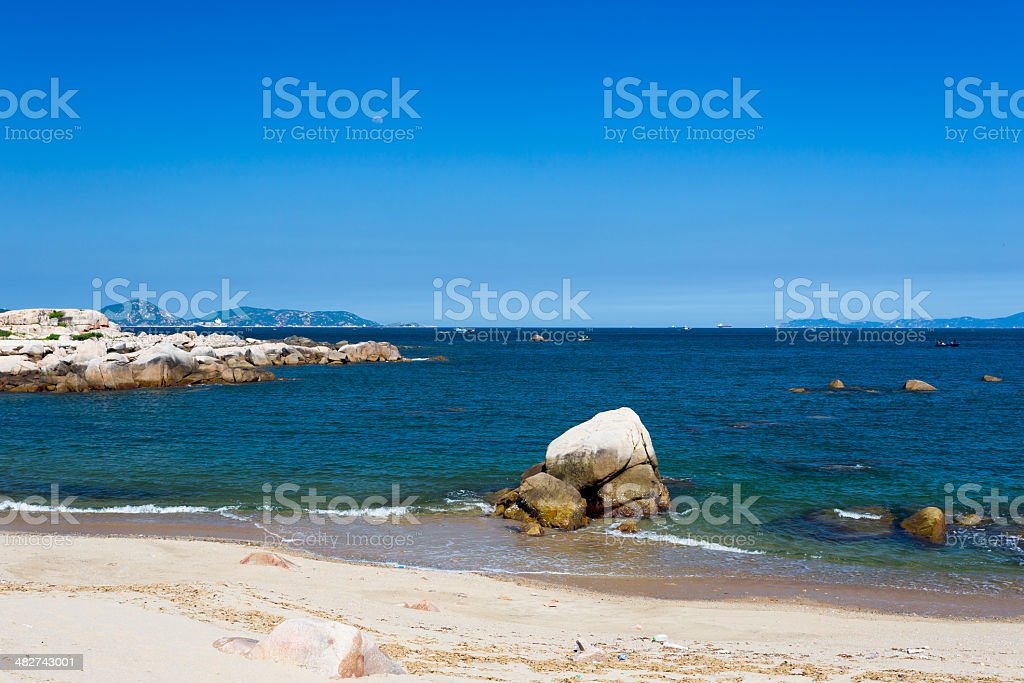 Tropical white sand beach with stone stock photo
