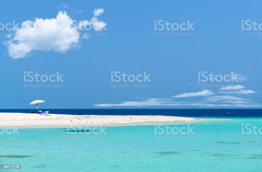 Tropical white sand cay beach with umbrella and a deep blue clear sky. Vacation related images and travel themes in the Caribbean. stock photo