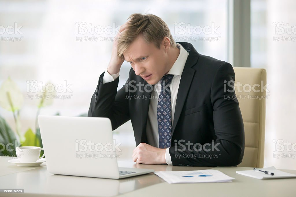 Troubled businessman with laptop stock photo