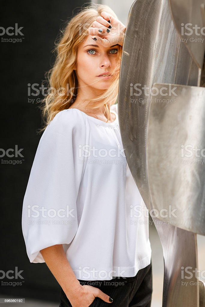 Troubled young businesswoman leaning on modernistic steel sculpture royalty-free stock photo