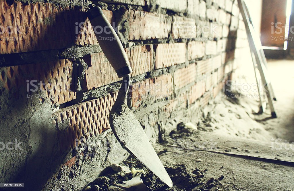 Trowel on a brick wall background stock photo